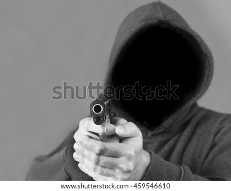 Violent hooded man points a firearm