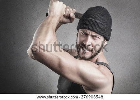 Violent man using a spanner or wrench as a weapon and looking at camera, close up head and shoulders - stock photo