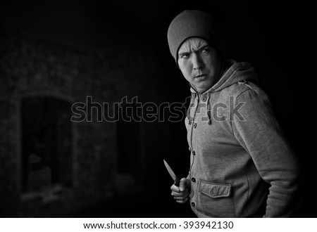 violent street crime, man with knife in front of abandoned building. Black and white portrait with copy space                    - stock photo