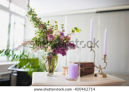 violet and white flowers in vase are standing on white chest drawers with candles in side