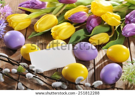 violet and yellow easter eggs with card, tulip and hyacinth - stock photo