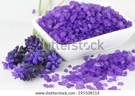 Violet bath salt in bowl on white wooden background. - stock photo