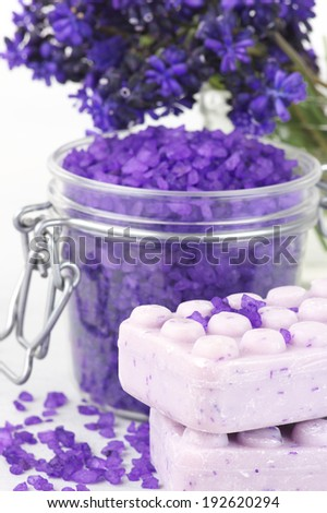 Violet bath salt in jar and soap close-up. Shallow DOF, focus on soap. - stock photo