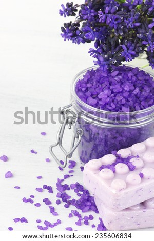 Violet bath salt in jar and soap on white wooden background. - stock photo