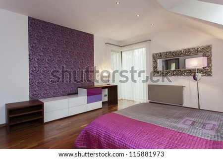 Violet bedroom with patterned wallpaper on one wall