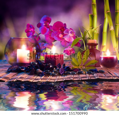 violet composition - candles, oil, orchids and bamboo on water - stock photo
