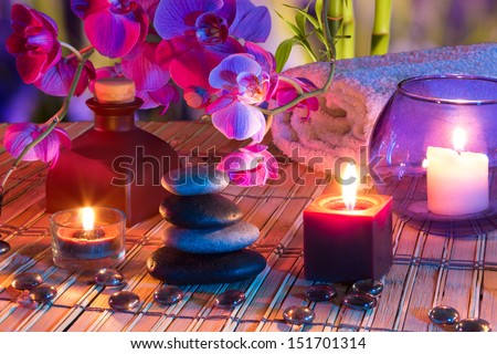 violet composition - candles, oil, potpourri, stones, glass dots, orchids and bamboo - stock photo