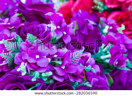 Violet fake flower handmade sewing flowers ,Lot of artificial flowers in colorful composition - stock photo