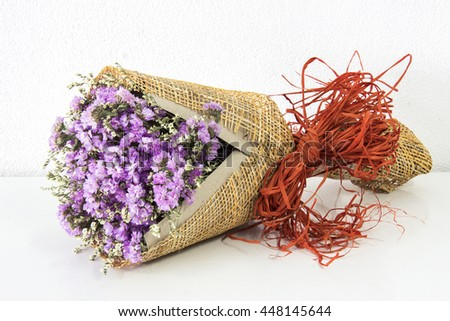 Violet flower bouquet, flower arrangement, violet Statice flower bouquet on white cement wall and white table background - stock photo
