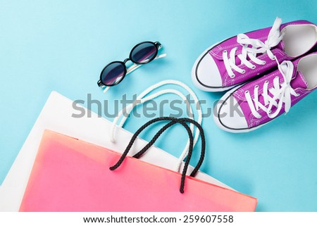 Violet gumshoes with white shoelaces and shopping bags with sunglasses on blue background. - stock photo