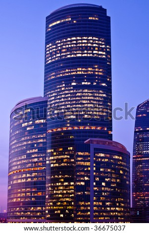 Violet-light modern skyscrapers at evening - stock photo