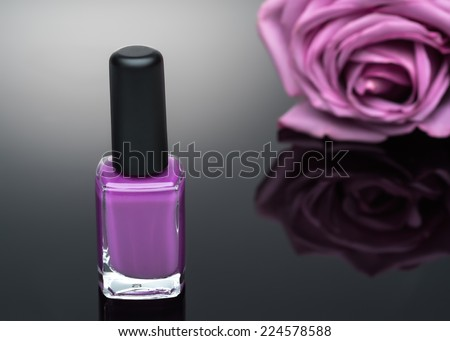 violet nail polish and rose on a black background - stock photo