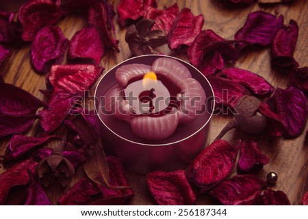 Violet scented candle with rose petals background, aromatherapy - stock photo