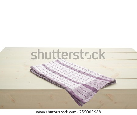 Violet squared tablecloth or towel over the surface of a wooden table, composition isolated against the white background - stock photo