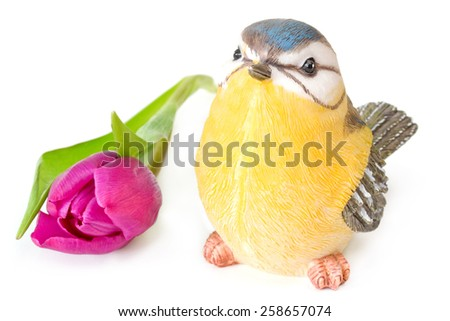Violet tulip with bird figurine on white background - stock photo