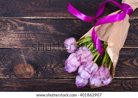 Violet tulips on a wooden  background. Free space for your text.