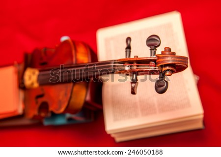 Violin and books on a red background - stock photo
