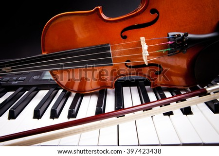 Violin and piano keys on black - stock photo