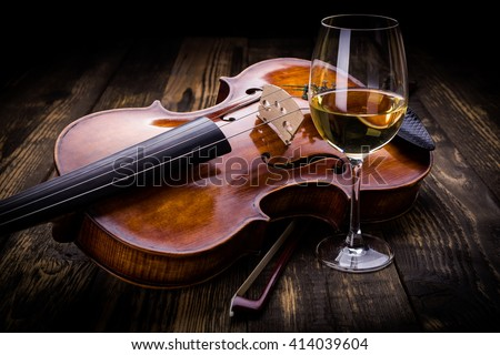 Violin and wine on dark wooden background - stock photo