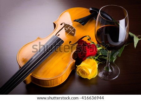 Violin, flower and red wine on shiny dark background - stock photo