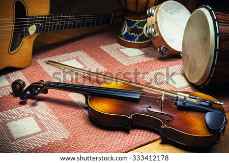 Violin, gypsy acoustic guitar and percussion instruments on tiled carpet, European and Balkan folk style.