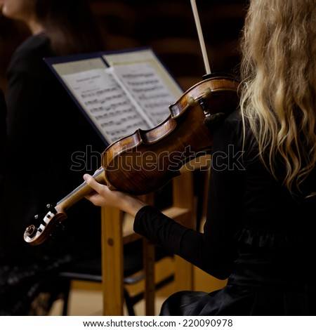 Violin in the hands of a girl in a symphony orchestra - stock photo
