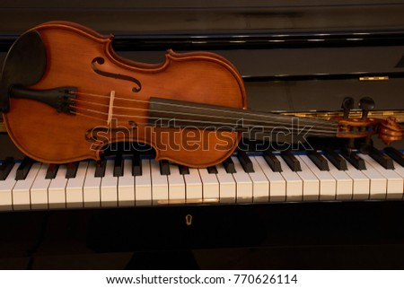 violin lies on a piano