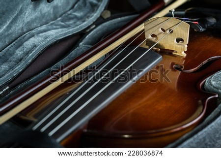 Violin lying in its case with bow on the side