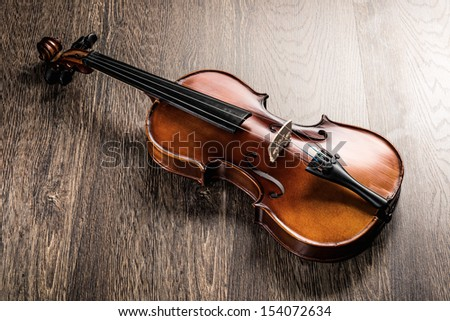 violin lying on a wooden textured table - stock photo