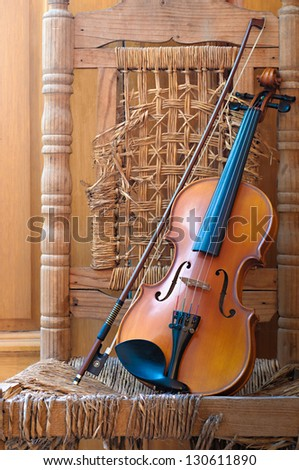 Violin lying on an old and ruined chair under window light - stock photo