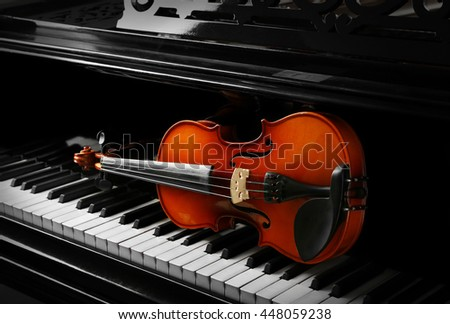 Violin lying on piano keys, close up