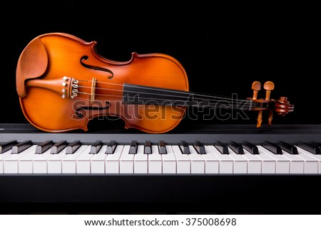 Violin on the piano on a black background