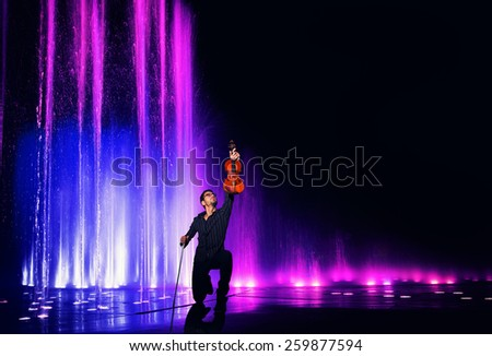 Violin performer with water and light show - stock photo
