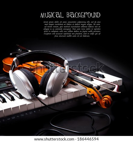 Violin, piano keys and headphones on black - stock photo