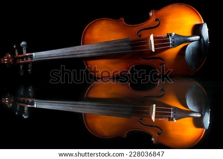 Violin stand on table with nice reflection and isolated on black background