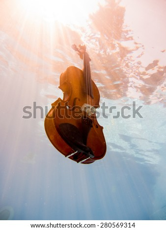 Violin underwater in the swimming pool - stock photo