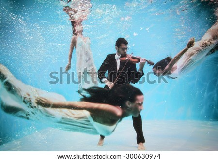 Violinist playing underwater with muse swimming around - stock photo