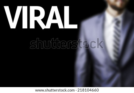 Viral written on a board with a business man on background - stock photo