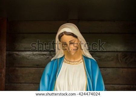 Virgin mary statue on wooden background - stock photo