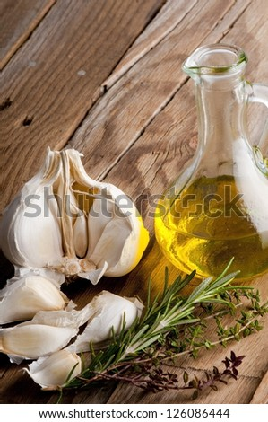 Virgin olive oil, garlic, rosemary and thyme on an old wooden board - stock photo