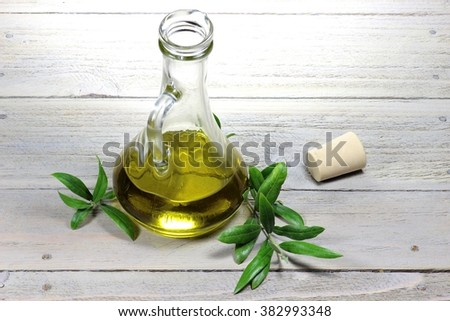 virgin olive oil in a glass carafe on wooden background - stock photo