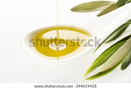 Virgin olive oil pouring on white spoon. - stock photo