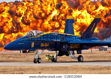 VIRGINIA BEACH - MAY 15:f-18  Blue Angels #1 with wall of fire in the background in Virginia Beach on May 15,2012 #1 plane is flown by the commander team is oldest demonstration group in the world - stock photo