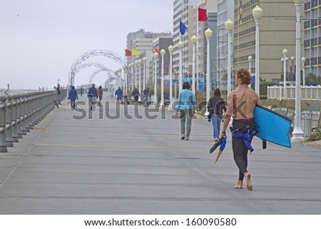 VIRGINIA BEACH, VIRGINIA, USA - OCTOBER 15, 2013: People walk along the Virginia Beach Boardwalk which parallels the ocean on a cloudy autumn day - stock photo