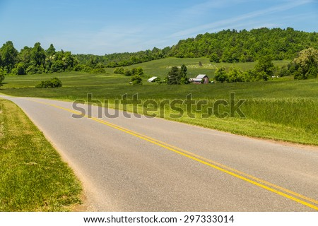 Virginia farmland along highway heading into Appalachian Mountains and Blue Ridge Parkway. Farm with family cemetery on hill in background. - stock photo