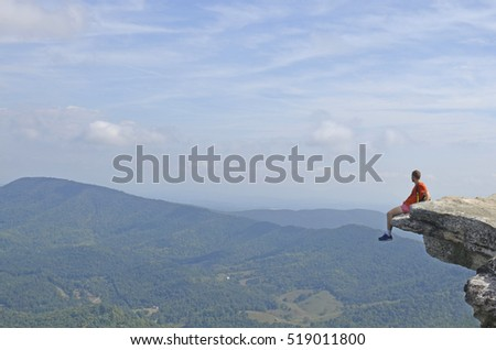 Virginia Tech hiker sits on the Mcafee Knob rock landmark in the Appalachian trail in south Virginia, USA