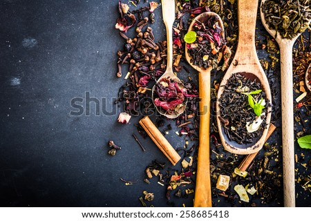 Virious kinds of tea in wooden spoons on black table - stock photo