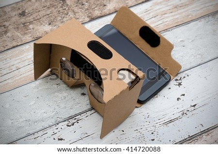Virtual reality cardboard glasses. Easy way to watch movies in 3D. Shoot on wooden background. - stock photo