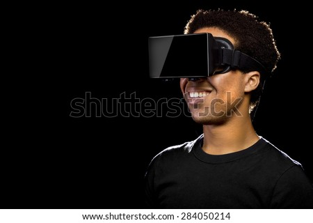 Virtual Reality headset on a black male playing video games - stock photo
