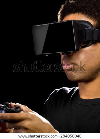 Virtual Reality headset on a black male with video game controller - stock photo